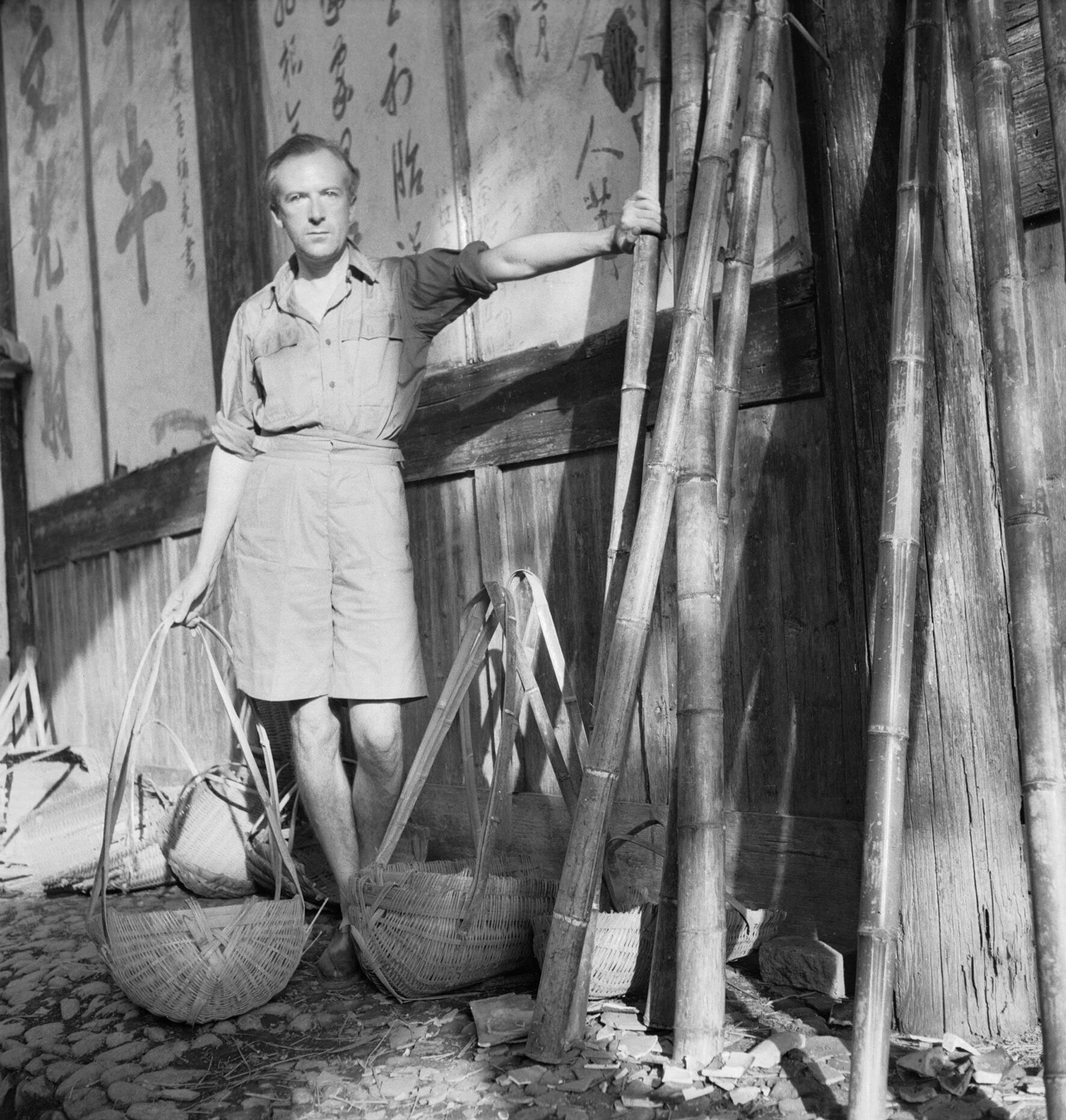 Cecil Beaton with wicker baskets beside a wall with Chinese characters in Puncheng in south eastern China, during World War II. Image courtesy of the Ministry of Information, via Wikimedia Commons