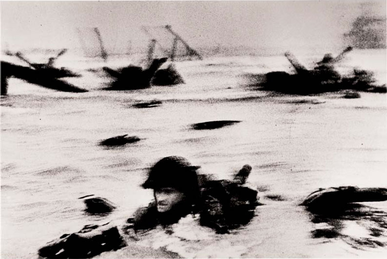 The first wave of American troops landing on D-Day,Omaha Beach, Normandy Coast, France, 6 June 1944 by Robert Capa. As reproduced in our Robert Capa book and in Magnum Stories